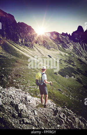 Rear view of male hiker during a trekking tour at the Bavarian Alps near Hochvogel and Bad Hindelang in Germany. - Stock Photo