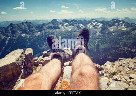 Climber in hiking boots on a rocky ledge overlooking the peaks of the Alps at Hochvogel, Germany, personal perspective - Stock Photo