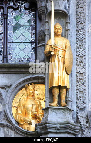 Golden statues of a knight and a damsel on the facade of the Basilica of the Holy Blood in Bruges, Belgium - Stock Photo