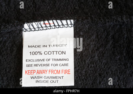 Close up label in black 100 % cotton fleece inflammable garment made in Turkey low cost manufactured product made - Stock Photo