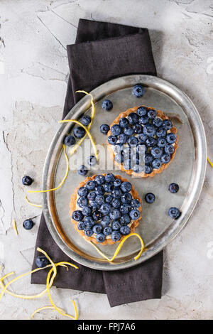 Two Lemon tartlets with fresh blueberries, served on vintage metal tray with lemon zest and black textile napkin - Stock Photo