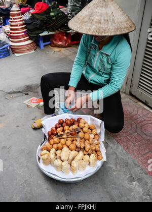 A Vietnamese woman selling donuts - Stock Photo