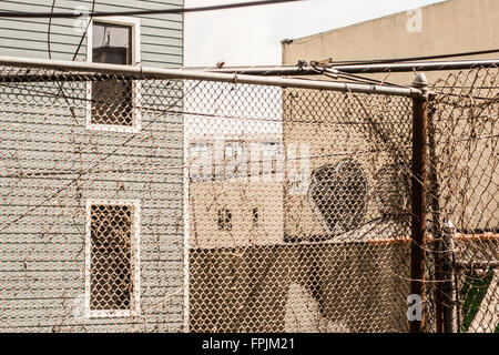 old chain link fence in a backyard in Brooklyn - Stock Photo