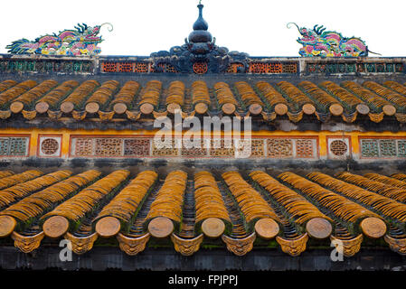 Decorated tiles and brightly coloured roof dragons on a temple at the Emperor Tu Duc Mausoleum, Vietnam - Stock Photo