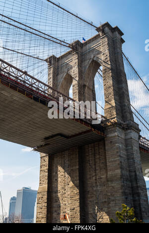 Looking up towards a tower of the Brooklyn Bridge in Dumbo, New York. - Stock Photo