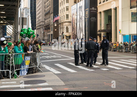 Police talking before the start of the annual St. Patrick's Day parade in New York City, with spectators looking - Stock Photo