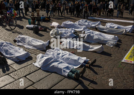 Turin, Italy. 19 mar, 2016: some demonstrators lie down on the ground and cover  themself with a white sheet in - Stock Photo