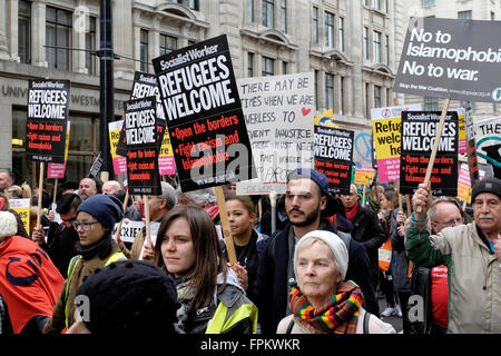 Protesters against racism march with placards reading 'Refugees welcome' - Stock Photo