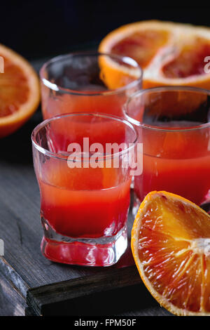Close up of Shorts of alcohol cocktail with Sliced Sicilian Blood oranges and fresh red orange juice, served on - Stock Photo