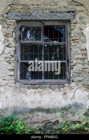 Window in old abandoned house with broken glass - Stock Photo