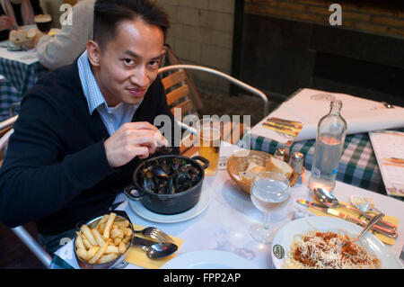 Asian tourist tasting the typical dish of Brussels: mussels and frites. Belgium. Rue des Bouchers. A couple in one - Stock Photo