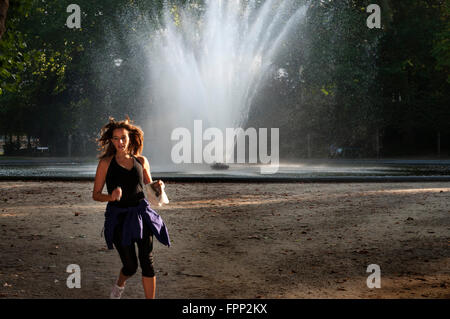 Woman running in the Warande park in front of the royal palace in Brussels Belgium on a hot summer day. Just in - Stock Photo