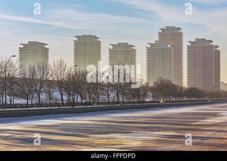 Picturesque morning scenery with modern high rise block of flats near frozen Dambovita river, in south-eastern Bucharest, - Stock Photo