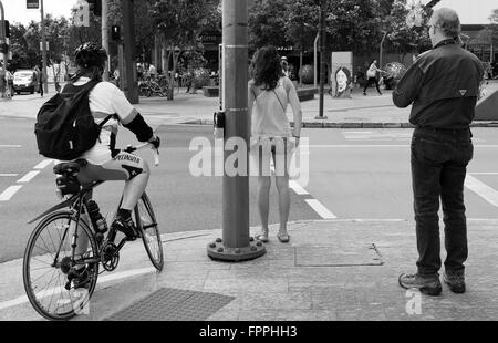pedestrians and cyclist wait at the lights at road crossing in Brisbane city - Stock Photo