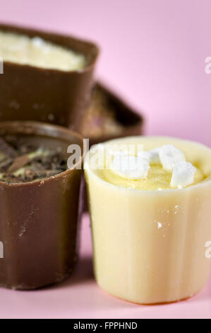 Close up of luxury continental or Belgian assorted chocolates on pink background - Stock Photo