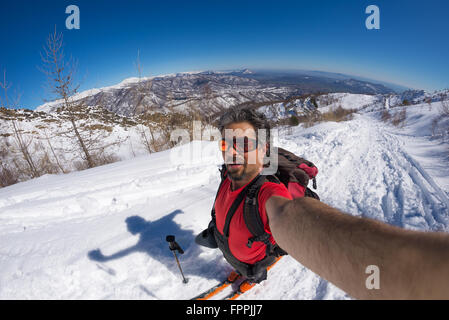 Adult alpin skier with beard, sunglasses and hat, taking selfie on snowy slope in the beautiful italian Alps with - Stock Photo