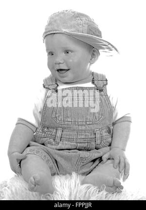 High key image of cute baby toddler  laughing and sitting on a sheepskin rug dressed in denim dungarees with a denim - Stock Photo