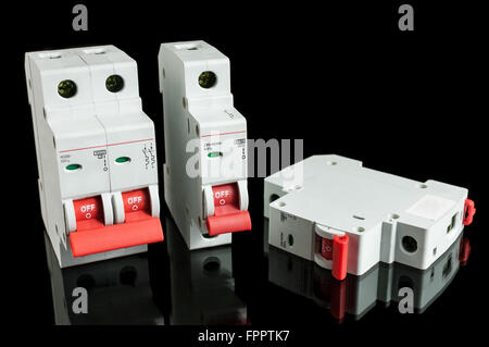 Various automatic circuit breakers, isolated on black background. Electric fuse. - Stock Photo