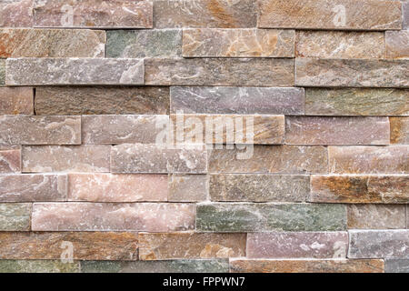 Detail of a stone wall of coarse, pastel-colored facing stones - Stock Photo
