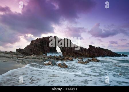 Brazil, Ceara, Jericoacoara, sunset at Pedra Furada rocks; crashing waves, rock arch - Stock Photo
