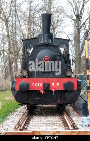 Front view on single old fashioned steam powered locomotive in outdoor museum display during winter - Stock Photo