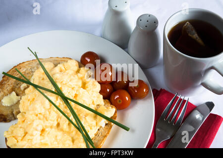 View of a typical English breakfast meal of Scrambled Egg on Toast with oven baked Cherry Tomato and a Chive garnish. - Stock Photo