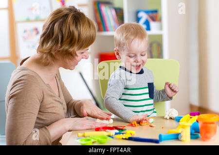KId boy and mother playing colorful clay toy - Stock Photo