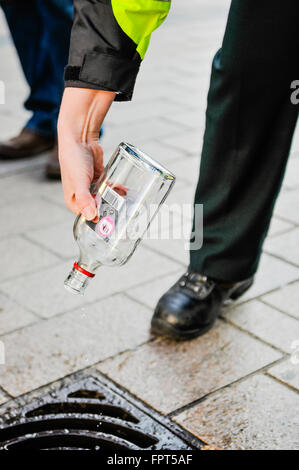 Belfast, Northern Ireland. 17 Mar 2016 - PSNI police officers dispose of alcohol confiscated from youths. - Stock Photo