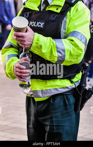 Belfast, Northern Ireland. 17 Mar 2016 - PSNI police officer carries a bottle of vodka and a cup as he disposes - Stock Photo