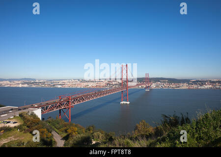 The 25 de Abril Bridge suspension bridge connecting city of Lisbon and Almada in Portugal, Tagus (Tejo) river - Stock Photo