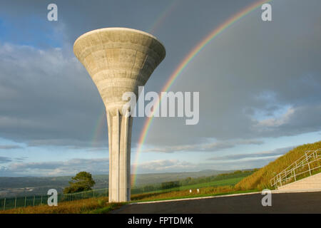 A concrete water tower in the foreground with a double rainbow in a cloudy blue sky on a sunny day - Stock Photo