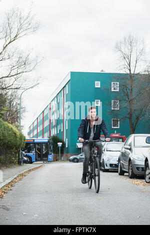 Young man riding bicycle on the street, Munich, Bavaria, Germany - Stock Photo