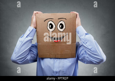 Businessman with cardboard box on his head with smiling expression concept for happiness, excitement, enthusiastic - Stock Photo
