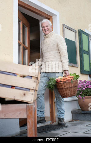 Portrait of a mature man holding basket full of vegetables in wholefood shop and smiling, Bavaria, Germany - Stock Photo