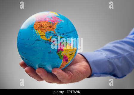 Businessman holding the world in the palm of his hands concept for global business, communications, politics, geography - Stock Photo