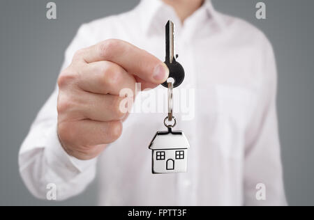 Man holding out house key on a house shaped keychain - Stock Photo