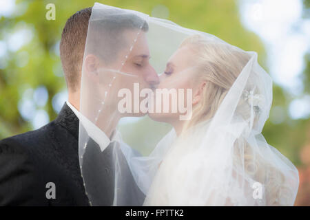 Close-up of a bride and groom kissing under veil, Ammersee, Upper Bavaria, Bavaria, Germany - Stock Photo