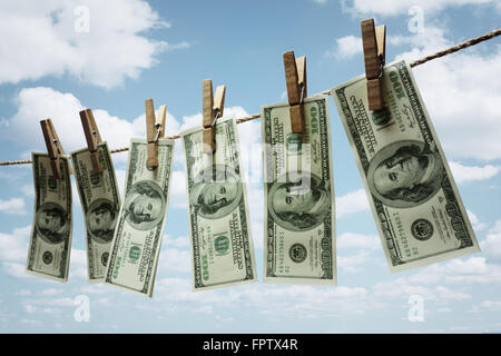Hundred dollar bills hanging from a clothesline concept for money laundering, investment or venture capital funding - Stock Photo