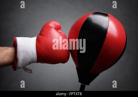 Punching a red punch bag concept for competition, challenge, conflict or leadership in business - Stock Photo