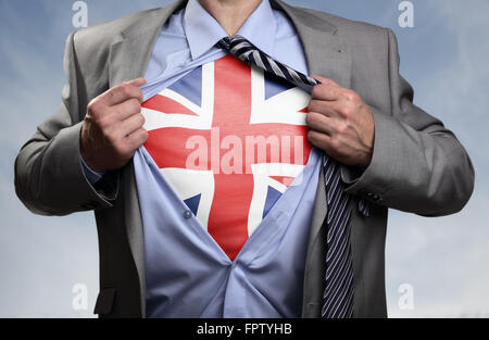 Superhero businessman revealing British flag - Stock Photo