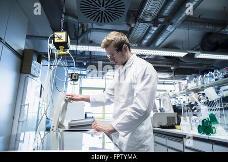 Young male scientist working in a pharmacy laboratory, Freiburg Im Breisgau, Baden-Württemberg, Germany - Stock Photo