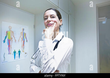 Female doctor thinking with hand on chin, Freiburg Im Breisgau, Baden-Württemberg, Germany - Stock Photo