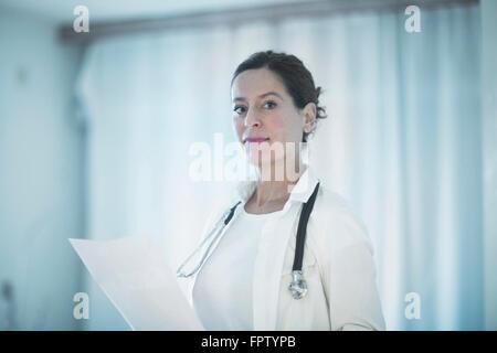 Portrait of a confident female doctor holding a medical report, Freiburg Im Breisgau, Baden-Württemberg, Germany - Stock Photo