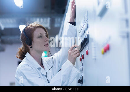 Young female engineer wearing headset and controlling a switch gear in control room, Baden-Württemberg, Germany - Stock Photo