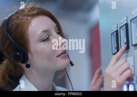 Young female engineer wearing headset and examining in control room, Freiburg Im Breisgau, Baden-Württemberg, Germany - Stock Photo