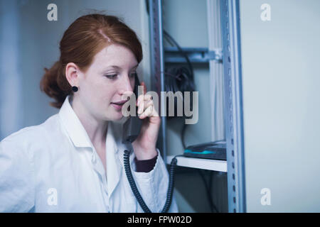 Young female engineer talking on landline phone in control room, Freiburg Im Breisgau, Baden-Württemberg, Germany - Stock Photo