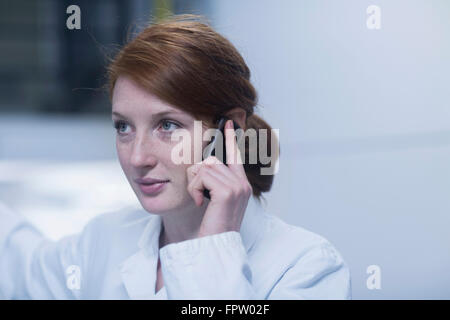 Young engineer talking on a mobile phone near switchgear in an industry, Freiburg im Breisgau, Baden-Württemberg, - Stock Photo
