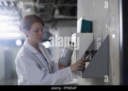 Young female engineer checking chemical bottles in a rack, Freiburg Im Breisgau, Baden-Württemberg, Germany - Stock Photo