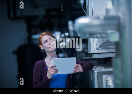 Young female engineer using a digital tablet and thinking in an industrial plant, Baden-Württemberg, Germany - Stock Photo