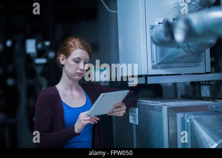 Young female engineer using a digital tablet in an industrial plant, Freiburg Im Breisgau, Baden-Württemberg, Germany - Stock Photo